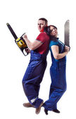 Man and woman with the saw and chainsaw are standing back to bac — Stock Photo