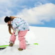 Young girl close snowboard fastering - Stock Photo