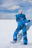 Snowboard girl in blue stay at the bottom of hill — Stock Photo