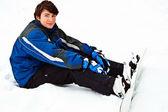 человек сидеть на снегу и подготовка к ездить — Стоковое фото