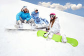Three young girls sit on snow — Stock Photo