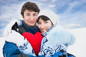 Smiling girl in blue embrase red heart and her friend — Stock Photo