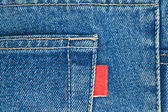 Blue old jeans pocket with empty red label — Stockfoto