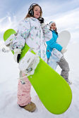 Girl in phones with green snowboard and her friend — Stock Photo