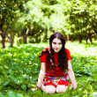 Girl in red dress seating in the grass — Stock Photo