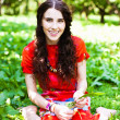 Girl in red dress seating in the grass and smiling — Stock Photo #4830775