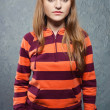 Portrait of young girl in striped sweatshirt and blue jeans - Photo