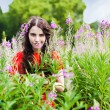 Smiling girl in red dress looking through the flowers on the mea — Stock Photo