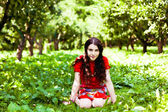 Fille en robe rouge assise dans l'herbe — Photo