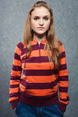 Portrait of young girl in striped sweatshirt and blue jeans — Stock Photo