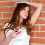 Beautiful woman against brick wall — Stock Photo