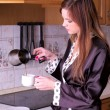 Beautiful young female make coffee at the home kitchen — Stock Photo