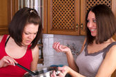 Two beautiful female trying to cook soup — Stock Photo