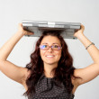 Portrait of young woman holding a laptop above her head — Stock Photo