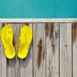 Sandals by a swimming pool - Stock Photo