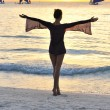 Girl on a beach at sunset - Stockfoto