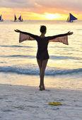 Meisje op een strand bij zonsondergang — Stockfoto