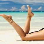 Women's legs on a beach — Stock Photo