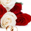 Wedding concept with roses and golden rings — Stock Photo
