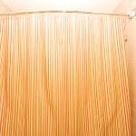 Bath tub behind striped colourful curtain — Stock Photo