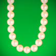 Pearl necklace against colourful background - Stock Photo