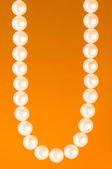 Pearl necklace against colourful background — Stock Photo