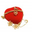 Red heart-shaped box and gold jewelery on white — Stock Photo