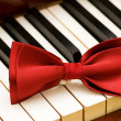 Red bow tie on the piano keys - Stock Photo