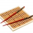 Red chopsticks on the mat isolated on the white — Stock Photo #4359460