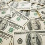 montón de billetes de dólar esparcidos sobre la mesa — Foto de Stock