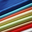 Stack of satin fabric of various colours - Stock Photo