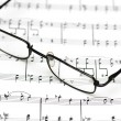 Stock Photo: Reading glasses over music sheets