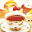 Cup of tea and various cakes -shallow DOF — Stockfoto