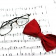 Bow tie and reading glasses on note paper — Stock Photo