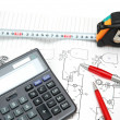 Calculator and pencils over the engineering drawings — Stock Photo