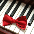 Red bow tie on white piano keys — Stock Photo