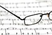 Black reading glasses over the music sheets — Stock Photo