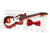 Musical notes, guitar and bow tie on white — Stock Photo