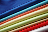 Stack of satin fabric of various colours — Stock Photo