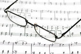 Reading glasses over the music sheets — Stock Photo