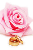 Two wedding rings and rose at background — Stock Photo