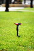 Water sprinkler on the green grass lawn — Stock Photo