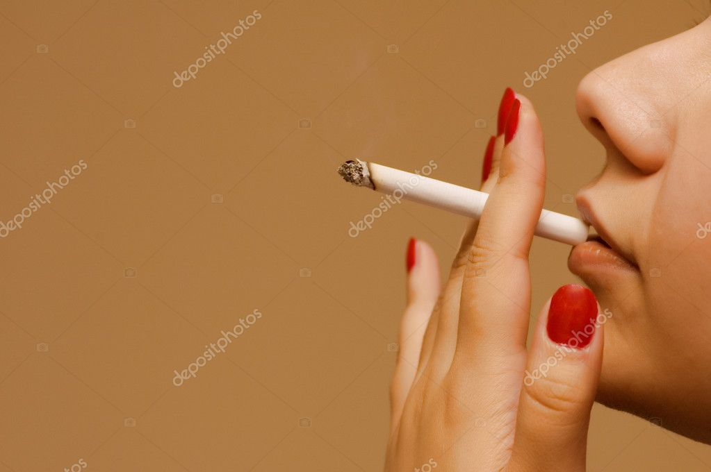 Woman smoking the cigarette on orange background  Stock Photo #4365036