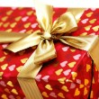 Close up of gift box with golden ribbon — Stock Photo