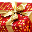 Close up of gift box with golden ribbon - Stock Photo