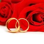 dva snubní prsteny a červené růže izolovaných na bílém — Stock fotografie