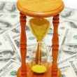 Time is money with dollar notes and hourglass — Stock Photo