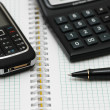 Mobile phone, calculator and pen on the notebook — Stock Photo