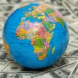 Globe isolated on background of dollar bank notes — Stock Photo #4376289