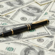Black ballpoint pen over dollar bank notes — Stock Photo #4377120